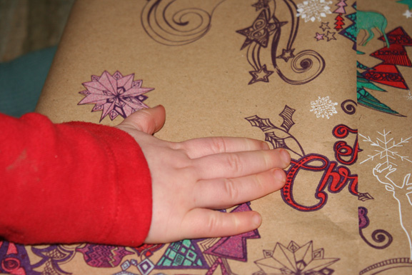 Toddler helping wrap gifts