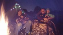 Family wrapped up warm in front of the campfire